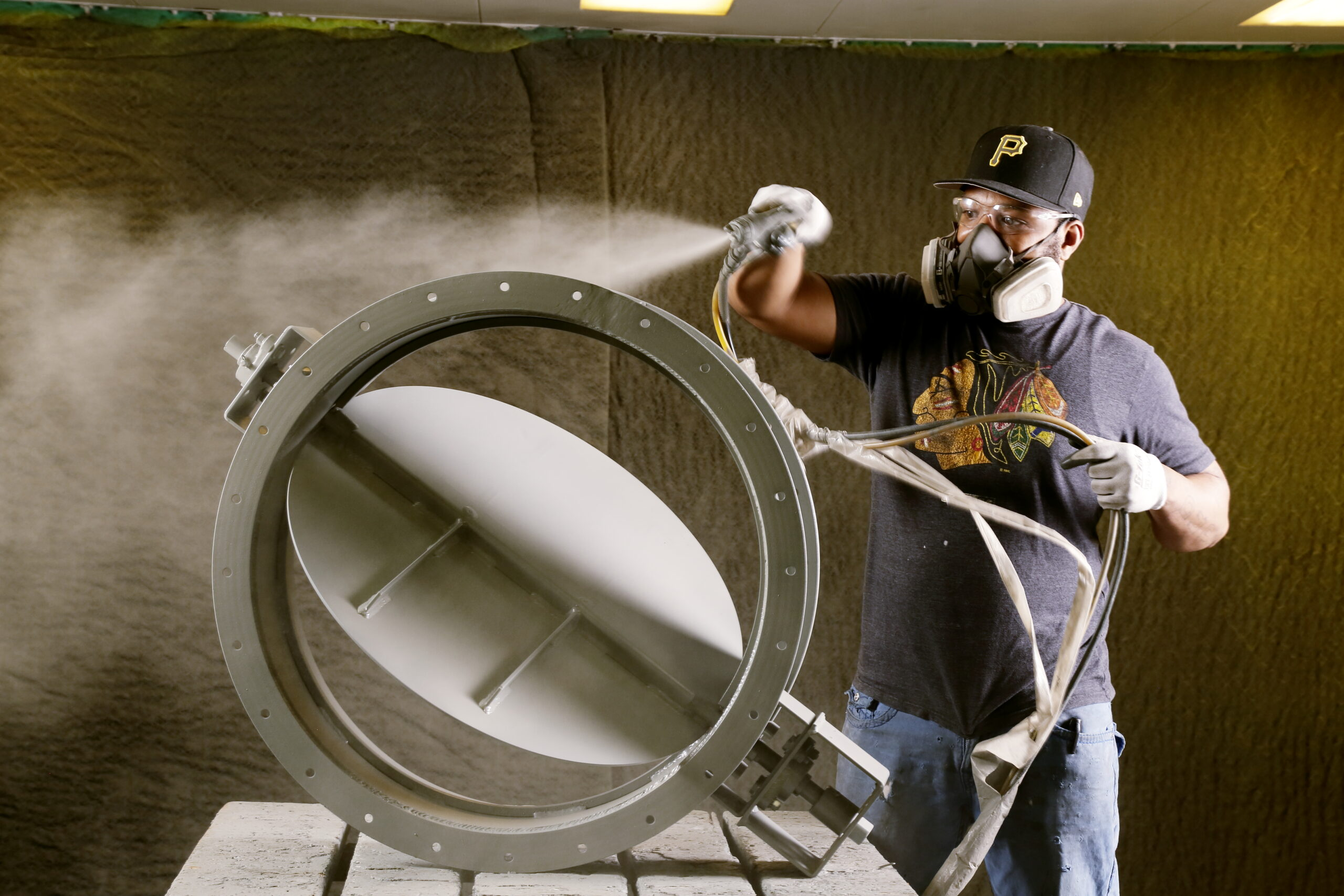 A Kelair shop worker polishing an industrial damper with a finishing product.