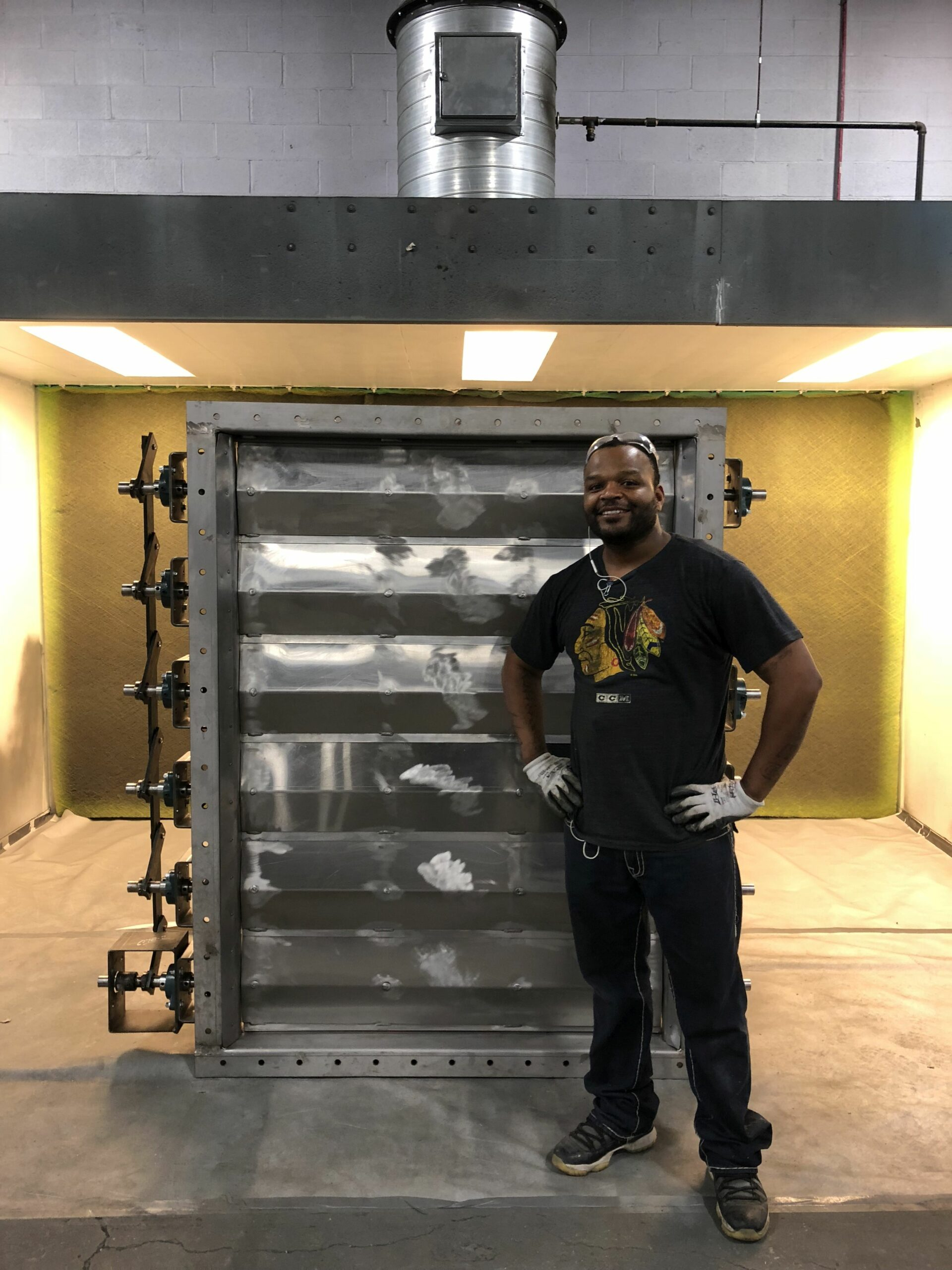 A Kelair shop worker smiles while standing next to a large louver damper.