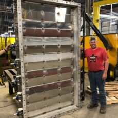 A Kelair shop worker smiles while standing next to a massive louver damper that is twice his size.