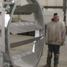 A Kelair shop worker smiles while standing next to a massive industrial damper.